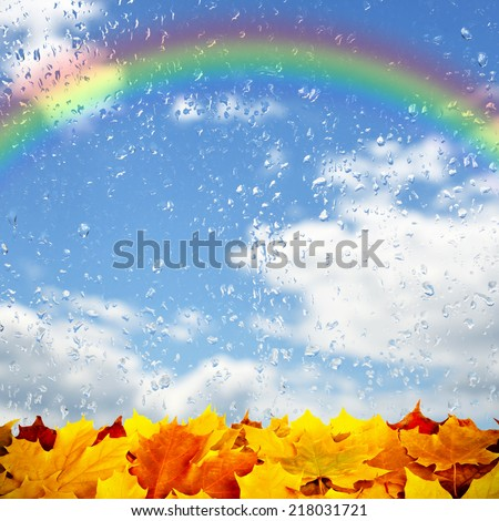 Autumn background with colorful leaves, raindrops and rainbow - stock photo