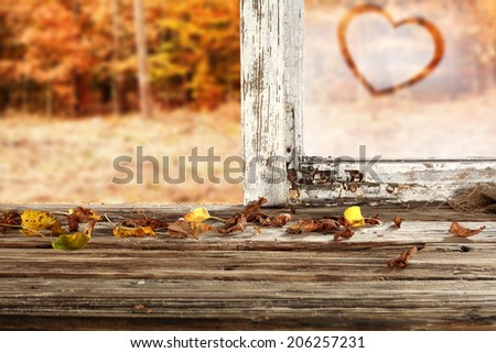 autumn background with leaves on window sill and heart  - stock photo