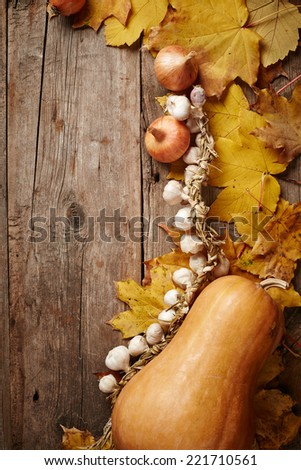 Autumn background with pumpkin, garlic and autumn leaves