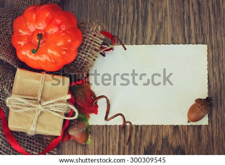 Autumn background with pumpkin, gifts and blank piece of paper - stock photo