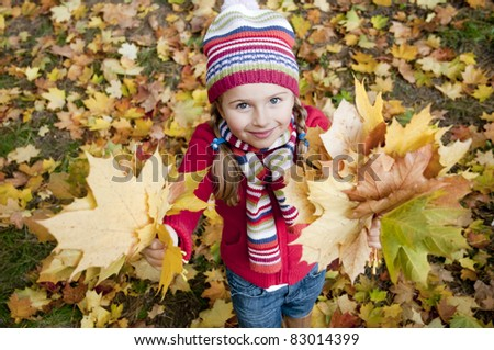 Autumn - Beautiful girl playing in autumn park - stock photo