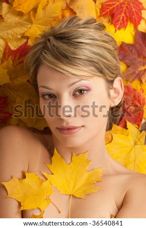 Autumn beauty. Portrait of attractive nudity woman covering by maple leafs