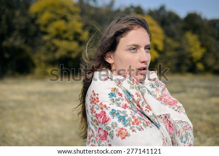 Autumn beauty: young pretty lady looking anxious on autumn forest copy space background - stock photo