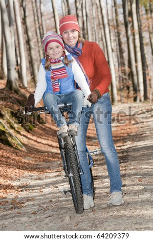 Autumn biking with mother - stock photo