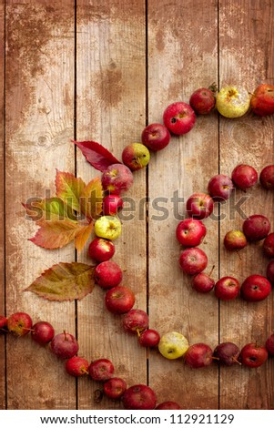 Autumn border from apples and fallen leaves on old wooden table with grunge texture/Thanksgiving day concept/background with apples - stock photo