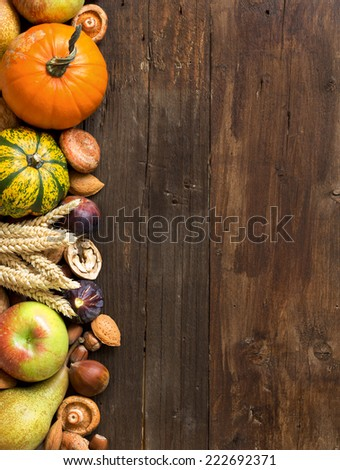 Autumn border made of fruits, vegetables, mushrooms, nuts and sunflower on a wooden table - stock photo