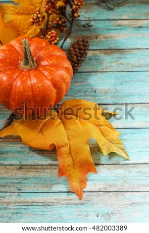 Autumn Border with Pumpkin maple leaves garland / Fall background on blue wooden background, selective focus
