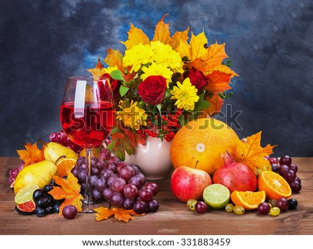Autumn bouquet, vegetables, pumpkins, grapes and wine in the glass on old table. - stock photo