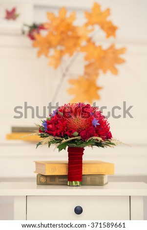 autumn bridal bouquet of red color with books on a dresser