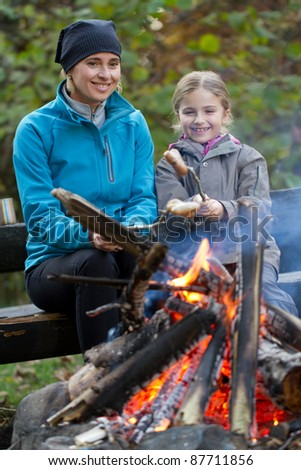 Autumn campfire - Mother and daughter are baking sausages at the bonfire - stock photo
