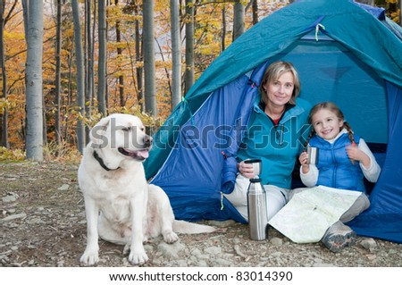 Autumn camping - family with dog in tent - stock photo