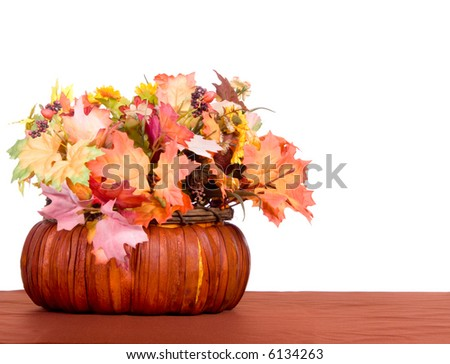 Autumn centerpiece of leaves and berries in a basket on brown table cloth - stock photo