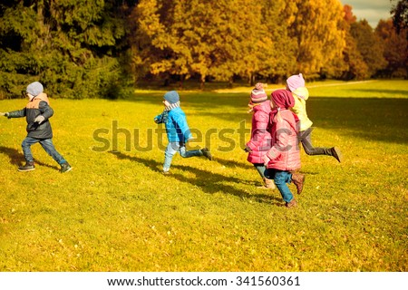 autumn, childhood, leisure and people concept - group of happy little kids playing tag game and running in park outdoors - stock photo