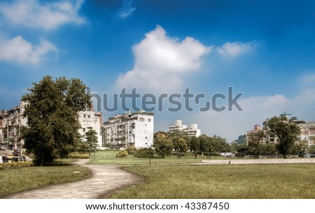 Autumn cityscape with apartment near park under the beautiful sky. - stock photo