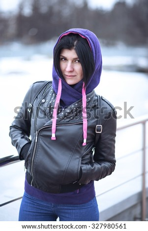 Autumn cloudy lifestyle. Portrait of a stylish young hipster woman on a street in the city, posing in a black leather jacket with leather. Close-up. Resting in the fresh air. The girl brunette.