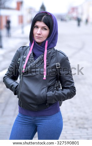 Autumn cloudy lifestyle. Portrait of a stylish young hipster woman on a street in the city wearing a fashionable outfit. Close-up. Resting in the fresh air. The girl brunette. - stock photo
