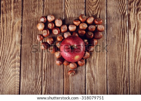 Autumn Collection. nuts and apple forming heart shape on wooden background - stock photo