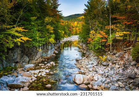 Autumn color and the Swift River at Rocky Gorge, on the Kancamagus Highway, in White Mountain National Forest, New Hampshire. - stock photo