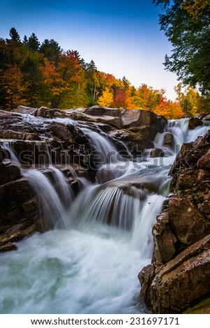 Autumn color and waterfall at Rocky Gorge, on the Kancamagus Highway, in White Mountain National Forest, New Hampshire. - stock photo