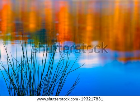 Autumn color reflects in calm lake in mountains of North Carolina - stock photo