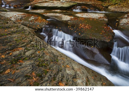 autumn colored leaf on the rock and pretty waterfall around - stock photo