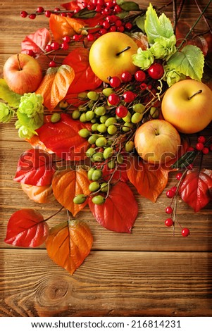 autumn colorful leaves, apples and mushrooms on wooden background - stock photo