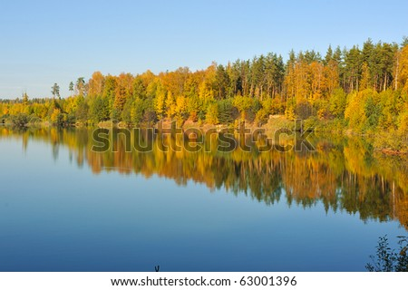 autumn colorful trees reflecting in blue  calm lake water - stock photo
