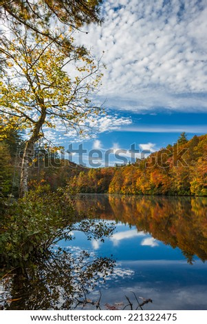 Autumn colors and clouds reflect in calm lake - stock photo