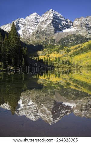 Autumn colors of Aspens reflecting in lake under Maroon Bells, Colorado, near Aspen - stock photo