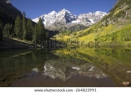 Autumn colors of Aspens reflecting in lake under Maroon Bells, Colorado, near Aspen - stock photo