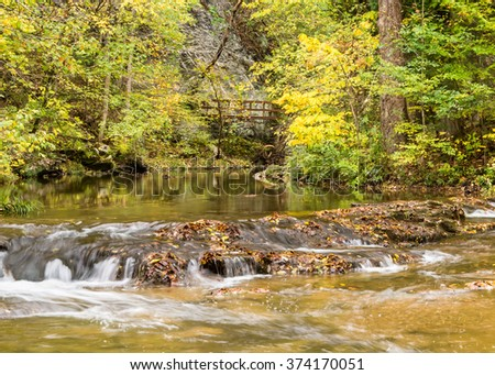 Autumn colors reflect in Cedar Creek, at Natural Bridge, Virginia. - stock photo