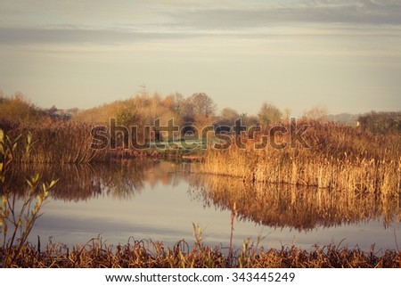 Autumn colors reflected on a timeless tranquil lake - stock photo
