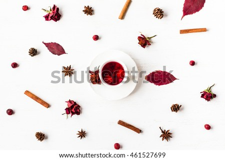 autumn composition with fruit tea cup, autumn leaves, cinnamon sticks, anise star, cones, dried rose flowers, top view, flat lay