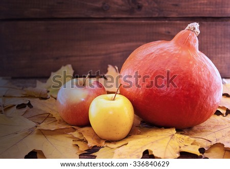 Autumn composition with pumpkin, yellow maple leaves and apple on rustic wooden table. Thanksgiving holiday and harvest concept.Selective focus. Toned image - stock photo
