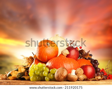 Autumn concept of traditional food. Mix of pumpkins, fruit and vegetable on wooden table with blur background. Free space for text - stock photo