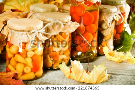 Autumn concept. Preserved food in glass jars on a wooden board. Marinated food - stock photo