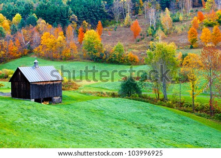 Autumn country scene with a vintage barn and colorful trees - stock photo