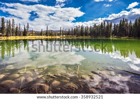 Autumn day in Jasper  National Park in the Rocky Mountains.  Small shallow lake surrounded by pine forest. The mirror surface of water reflects the cloudy sky - stock photo