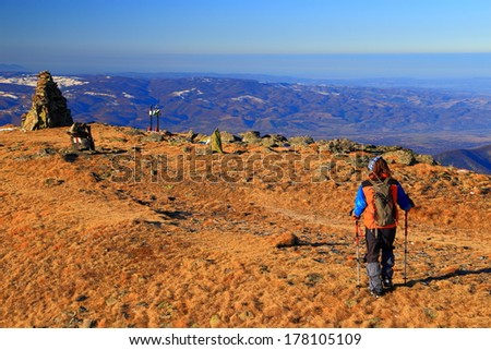Autumn day on the mountains, with hiker heading to the summit