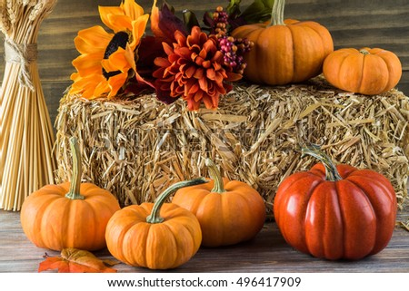 Autumn decor with natural straw bale, pumpkins, flowers.