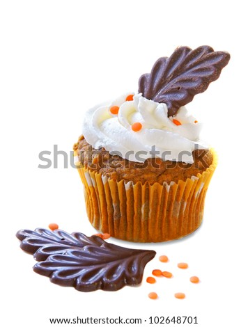 Autumn decorated cupcake with chocolate leaves and orange sprinkles - stock photo