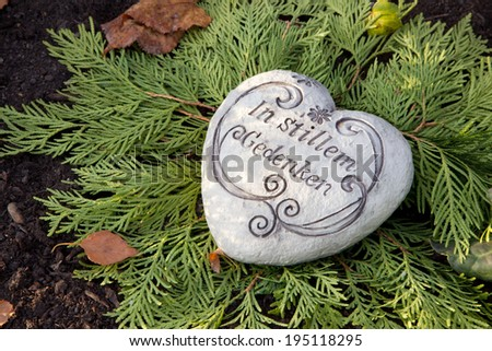 Autumn decoration on the tomb with white heart and german text on it. - stock photo