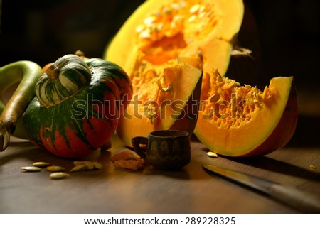 Autumn decorations with pumpkins - orange pulp and seeds on rustic surface - stock photo