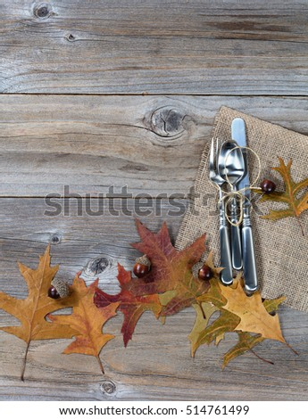 Autumn dinner place setting for Thanksgiving holiday in vertical layout on rustic wooden boards.