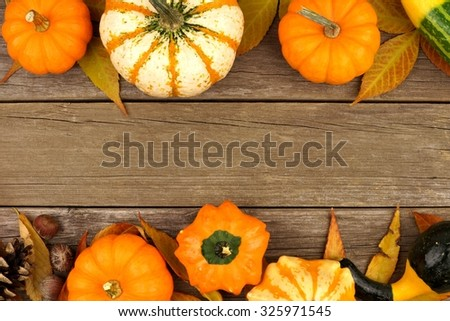 Autumn double border of pumpkins, leaves and gourds against a rustic wood background