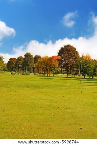 Autumn Fairway, a bright Autumns Day with Golfer walking up the Fairway with Golf Ball near Flag. Plenty of space for Text - stock photo