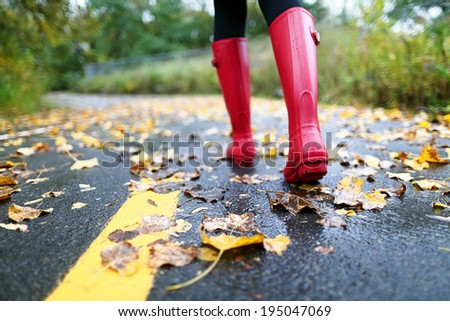 Autumn fall concept with colorful leaves and rain boots outside. Close up of woman feet walking in red boots. - stock photo