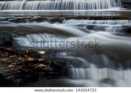 Autumn Fall Just one of many picturesque waterfalls on the Presque Isle River in the Porcupine Mountain Wilderness Area, Michigan. - stock photo