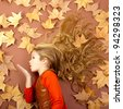 autumn fall little blond girl on dried tree leaves blowing wind with lips - stock photo
