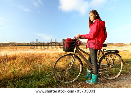Autumn / fall woman biking on bicycle near field in beautiful landscape. Beautiful young mixed race Caucasian Asian girl. Danish summer landscape near Randers, Denmark. - stock photo
